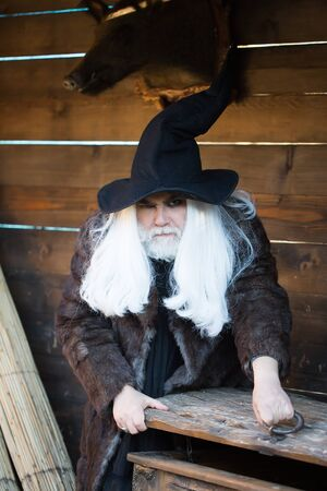 log house: Brutal druid old man with long silver hair and beard in black Halloween hat opens vintage wooden chest on log house background Stock Photo