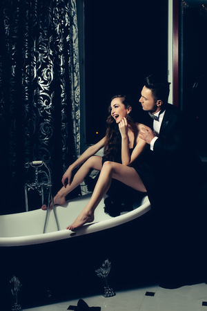 dress suit: young handsome man in black suit and bow with pretty sexy woman in elegant evening dress with skirt and long curly hair sitting in bath Stock Photo