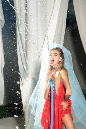 young sexy woman bride with pretty face and long blonde hair, in red dress and blue veil holding hose with water drops outdoor in evening Imagens