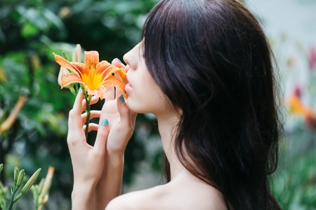 enjoys: Sensual woman with long brunette hair enjoys fragrance of lily bright orange flower blossoming in summer garden on natural background