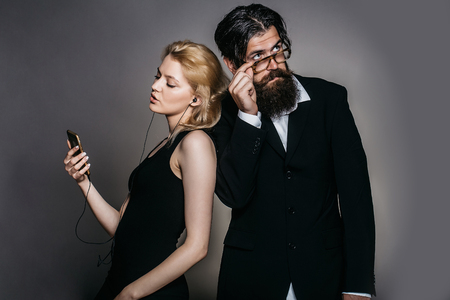 listens: Elegant couple of young blond woman in black dress listens to music in smartphone with earphones and handsome bearded hipster man in glasses suit stand together on grey wall Stock Photo