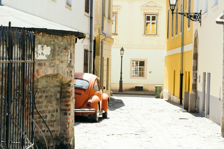 Narrow street and old houses with retro car in medieval town on sunny day on streetscape background Reklamní fotografie