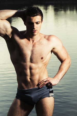 six packs: handsome young macho man with muscular sexy body and six packs on torso in pants sunny day outdoor on water natural background Stock Photo