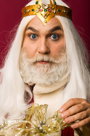 old bearded zeus man wizard in jewellery golden crown with blue lenses in eyes with long gray beard and white hair has serious surprised face on purple background