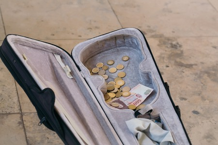 fiddles: Violin case with paper money and coins on street pavement background Stock Photo