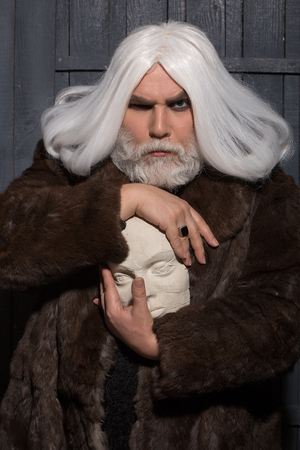 druid: old druid bearded man with long beard on serious face and hair in fur coat holding white sculpture head in hands with ring on wooden background Stock Photo