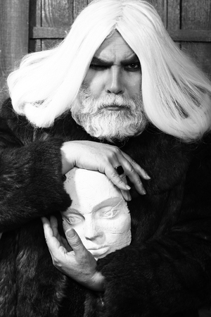 old druid bearded man with long beard on serious face and hair in fur coat holding sculpture head in hands with ring on wooden background, black and white