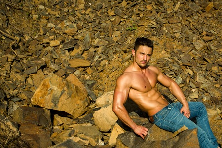 six packs: handsome young macho man with muscular sexy body and six packs on torso in jeans sunny day outdoor on stony natural background