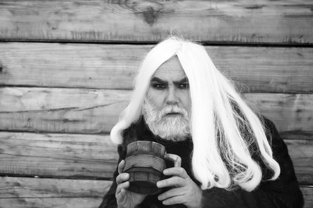 Druid old man with long grey hair and beard on serious face with wooden mug in hands outdoor on wood background, black and white