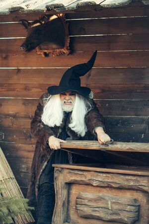 opens: Brutal druid old man with long silver hair and beard in black Halloween hat opens vintage wooden chest on log house background Stock Photo