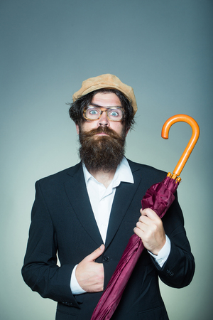 wears: Handsome man bearded hipster male wears vintage cap glasses black suit with umbrella cane on grey wall