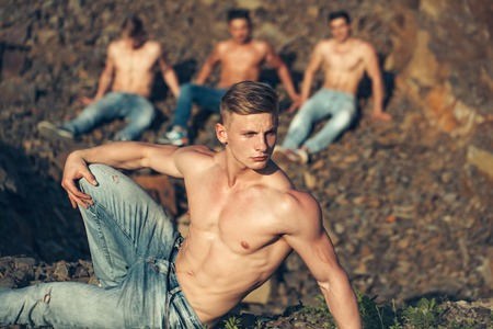 six packs: four handsome young macho men with muscular sexy body and six packs on torso in jeans sunny day outdoor on stony natural background