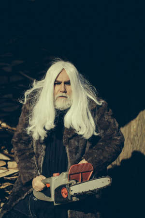 silver hair: Old man druid with long silver hair and beard in fur coat holding big chainsaw sunny day outdoor
