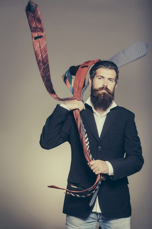 Handsome man with serious face and splendid beard holding many fashion colorful ties in his hands posing in studio on gray background Stok Fotoğraf