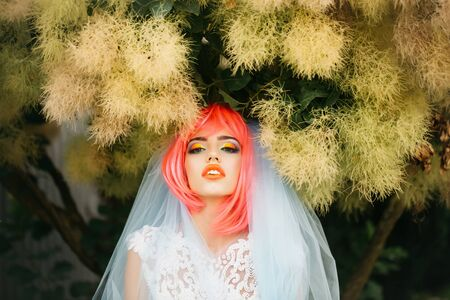 fur tree: young woman with orange or pink hair and bright makeup on pretty face in white wedding dress and blue bride veil on natural green fur tree background outdoor Stock Photo