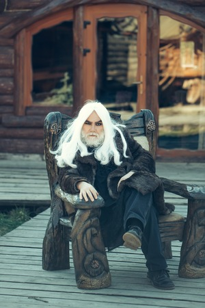 house coat: Old bearded man wizard with long white hair and beard in fur coat sits in wooden chair on log house background Stock Photo