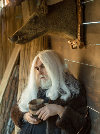 silver hair: Old druid man with long silver hair and beard holds wooden mug on stuffed boar head background