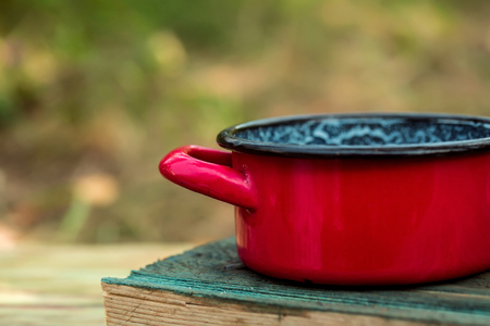 stockpot: Vintage red enamel pan for cooking on wooden board on natural background