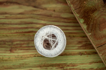 Spool with white iris yarn on wooden table on timber background 写真素材