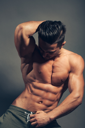 six packs: handsome young macho man with muscular sexy body and six packs on torso in pants in studio on grey background Stock Photo
