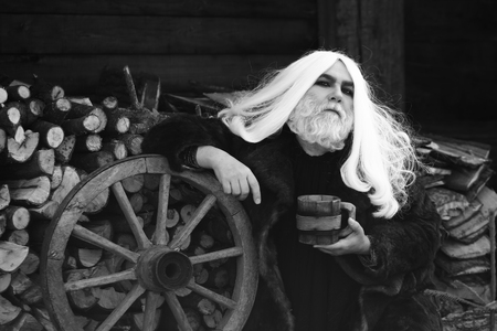druid: Druid old bearded man with long grey hair and beard in fur coat with wooden mug in hands near wheel outdoor, black and white