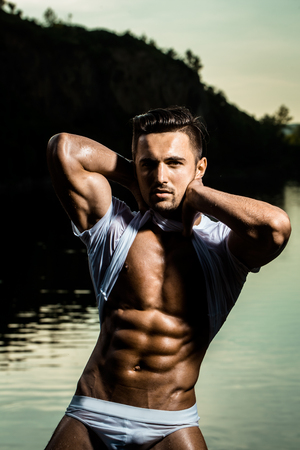 six packs: handsome young macho man with muscular sexy body and six packs on torso in pants and wet shirt sunny day outdoor on water natural background Stock Photo