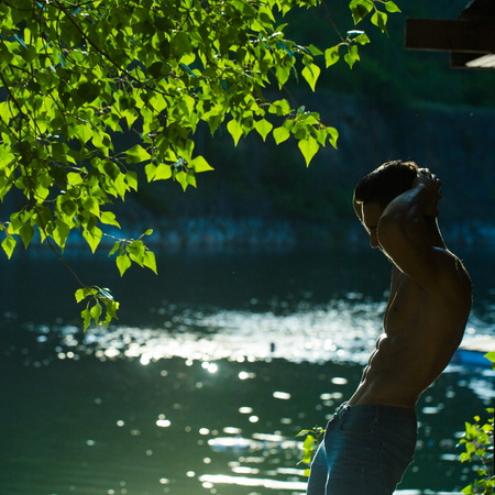 six packs: handsome young macho man with muscular sexy body and six packs on torso in jeans sunny day outdoor on water natural background