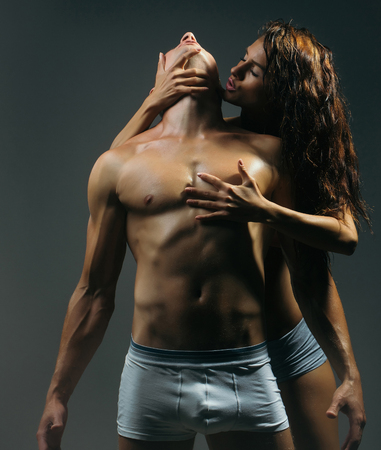 young sexy couple of pretty slim sporty woman with long curly hair and handsome muscular man with fit body and bare chest with torso in panties on studio background