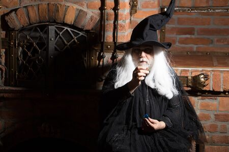 pendulum: Old wizard with pendulum in black costume and hat for Halloween on kitchen background