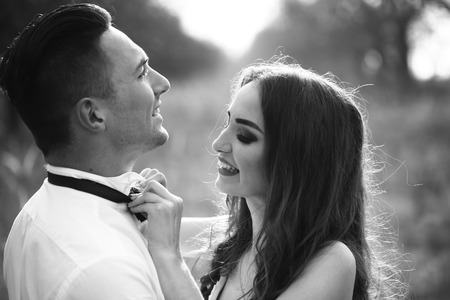 undressing woman: Young happy wedding couple of pretty woman and man undressing in field outdoor, black and white