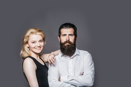 long beard: young couple of woman with pretty smiling face and blonde hair in black vest and handsome bearded man with long beard in white shirt in studio on grey background Stock Photo