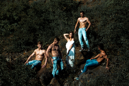 six packs: four handsome young macho men with muscular sexy body and six packs on torso in jeans and pretty woman in white dress sunny day outdoor on green natural background Stock Photo