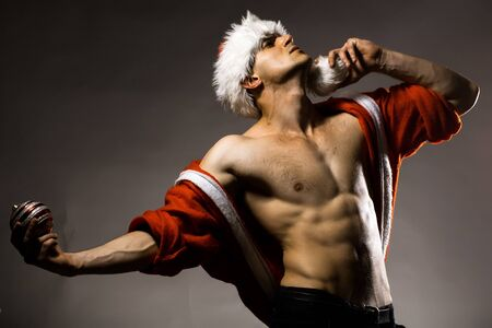 sexy santa claus: Young handsome man with muscular body bare chest and torso in santa claus coat and hat posing in studio on grey background