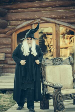 evil man: Evil man wizard with long grey hair beard in black costume and hat for Halloween outdoors on log house background Stock Photo