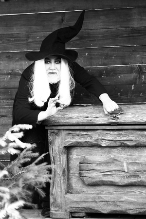 chest hair: Old man wizard with long grey hair beard in black costume and hat for Halloween standing near wooden chest or trunk box on log house background, black and white