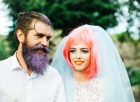 Paar der jungen hübschen Glamour lächelnde Braut mit rosa Haaren in weißen Brautschleier und ein stattlicher Bräutigam mit lila gefärbten Bart im Freien Standard-Bild