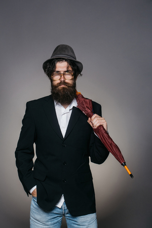 wears: Handsome man bearded hipster male wears vintage hat glasses black suit with umbrella cane on grey wall