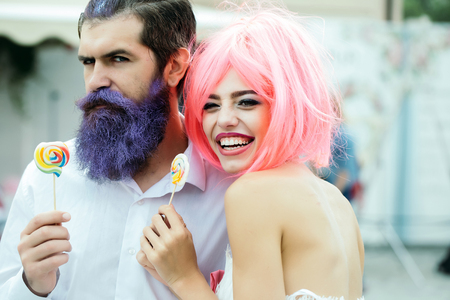young glamour happy couple of pretty woman with orange hair and bearded handsome man with blue beard eating lollipop candies Stock Photo