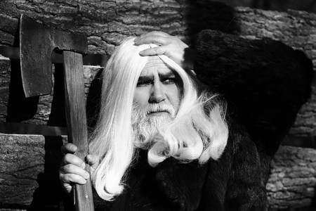 silver hair: Old man druid with long silver hair and beard in fur coat holding big sharp axe on wooden house background sunny day outdoor, black and white