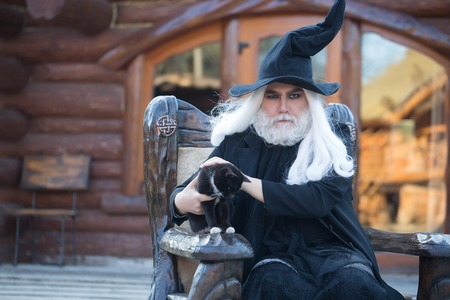 sits on a chair: Evil wizard in black costume hat for Halloween holds cat and sits in wooden chair on log house background