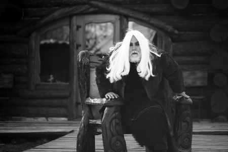 sits on a chair: Old bearded man wizard with long hair and beard in fur coat sits in wooden chair on log house background, black and white