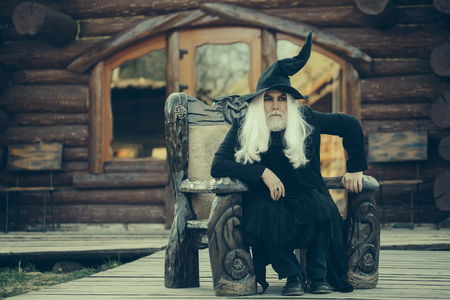 sits on a chair: Old man wizard with long grey hair beard in black costume and hat for Halloween sits in wooden chair on log house background