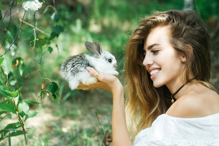 Pretty young woman long-haired holds cute little rabbit on summer day on natural background