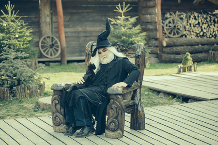 sits on a chair: Old man in wizard costume hat for Halloween strokes black cat and sits in wooden chair on natural background Stock Photo