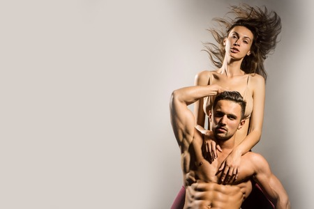 desire: young sexy couple of pretty woman in beige bra with wet hair and handsome macho man with muscular torso and athletic body in studio on grey background, copy space