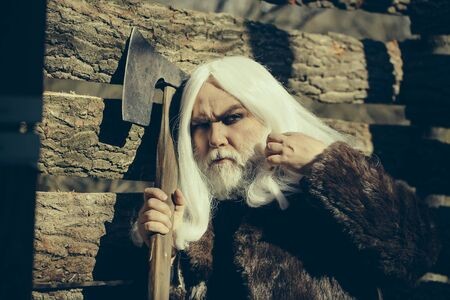 steel: Old man druid with long silver hair and beard in fur coat holding big sharp axe on wooden house background sunny day outdoor