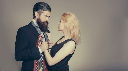 long beard: young fashionable couple of woman with pretty face and blonde hair and handsome bearded man with long beard in black jacket and tie in studio on grey background, copy space