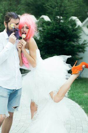 funny bearded man: Happy bride with pretty face in funny pink wig white bridal dress and veil with handsome young groom with lilac colored beard and hair on their wedding with lollipops in hands Stock Photo