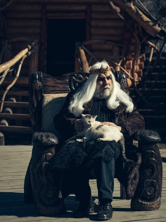log house: Druid old man with long grey hair beard with crown in fur coat holds cat and sits in wooden chair on log house background