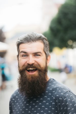 pancreatic cancer: handsome sexy bearded young man hipster with long beard and mustache has stylish hair on smiling hairy face outdoor, closeup Stock Photo